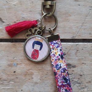 Porte-clés bronze Kokeshi tons rouge-mauve