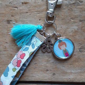 Porte clés kokeshi Bleu-vert ruban fleuri fond blanc